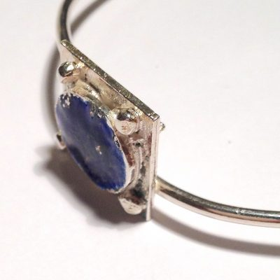 Sterling silver round wire closed bangle with square reticulated silver and deep blue enamel detail.