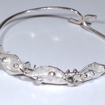 ELB108 - Sterling silver round wire bangle with three reticulated leaves detail.